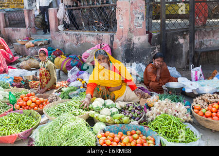 Old local Indian woman dressed in colourful traditional clothes selling vegetables at a roadside market in Deogarh, - Stock Photo
