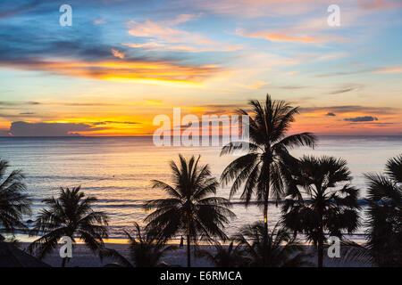 Sunset over the sea, Surin Beach, Phuket, Thailand with silhouettes of palm trees against a vivid multi-coloured - Stock Photo