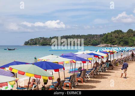 Colourful beach umbrellas, sunshades, parasols and sunloungers on the seashore in Surin Beach, Pkuket, Thailand - Stock Photo