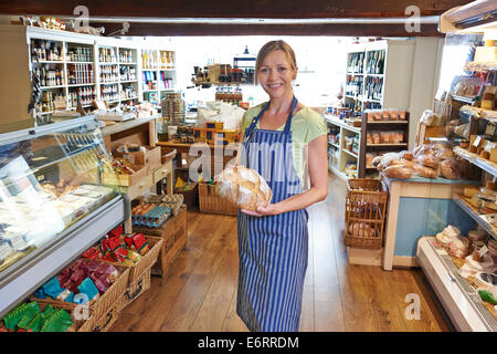 Owner Of Delicatessen Standing In Shop Holding Loaf Of Bread - Stock Photo