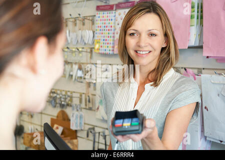 Shopper Paying For Goods Using Credit Card Machine - Stock Photo