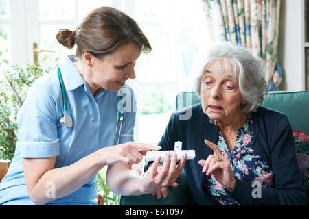 Nurse Advising Senior Woman On Medication At Home - Stock Photo