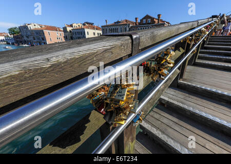 Love padlocks on the Ponte di Academia or the academia bridge which spans the Grand canal in Venice, Italy. - Stock Photo
