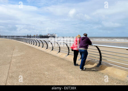 Middle aged couple on the promenade in Blackpool looking out to sea. North Pier is in the background - Stock Photo