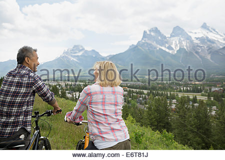 Couple standing with mountain bikes on hillside - Stock Photo