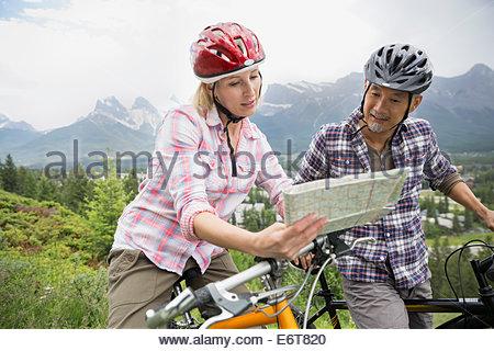 Couple on mountain bikes reading map on hillside - Stock Photo