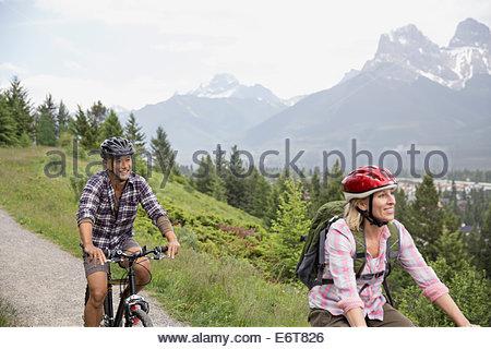 Couple riding mountain bikes on hillside - Stock Photo