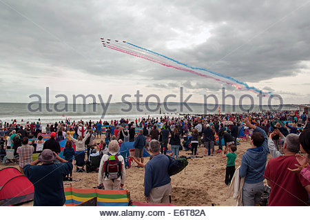 The crowd cheers and waves as the RAF Red Arrows team of eight planes perform at the Bournemouth Air Show, 30th - Stock Photo