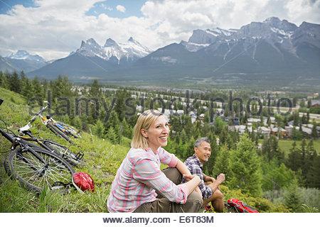 Couple with mountain bikes sitting on hillside - Stock Photo