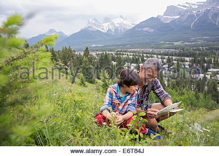 Father and son reading map on rural hillside - Stock Photo
