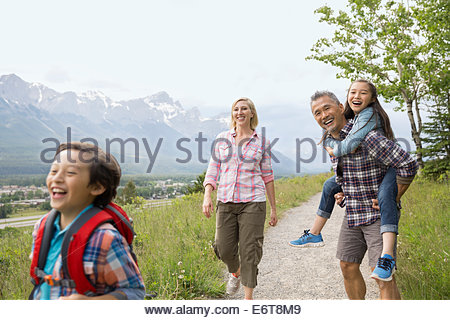 Parents and daughter walking on dirt path - Stock Photo