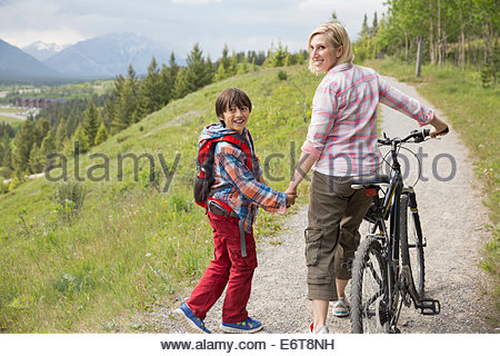 Mother and son walking on dirt path - Stock Photo