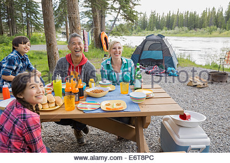Family eating together at campsite - Stock Photo