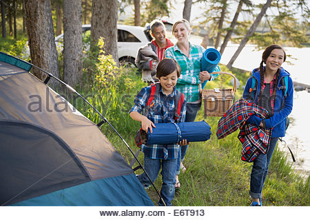 Family carrying gear at campsite - Stock Photo