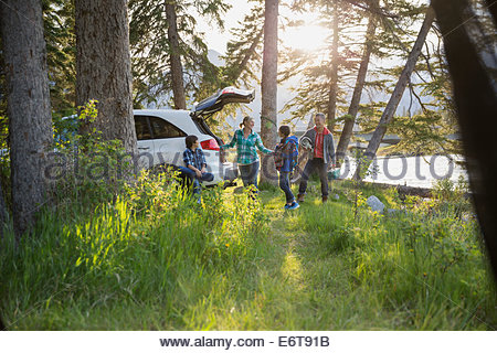Family unpacking car at campsite - Stock Photo