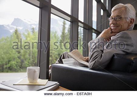 Businessman reading newspaper near lobby window - Stock Photo