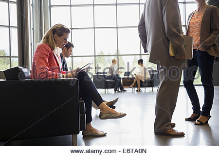 Business woman using digital tablet in office lobby - Stock Photo