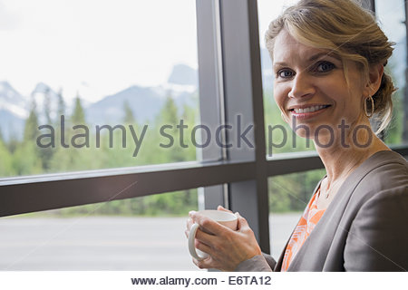 Businesswoman having cup of coffee near window - Stock Photo