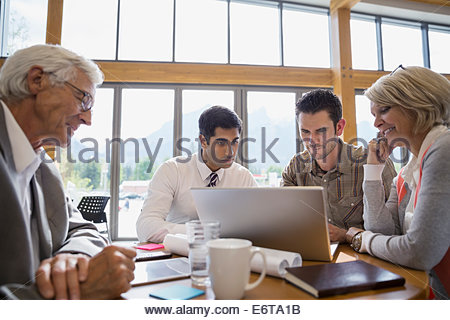 Business people using laptop in meeting - Stock Photo