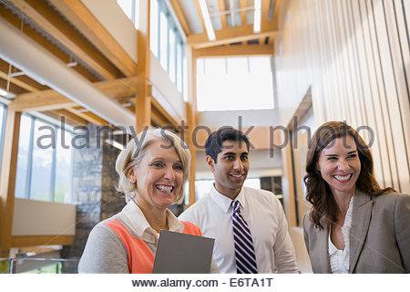 Business people smiling in office lobby - Stock Photo