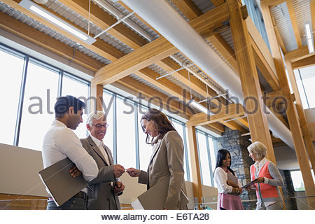 Business people exchanging business cards in office lobby - Stock Photo