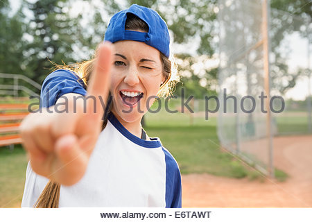 Baseball player holding up index finger on field - Stock Photo