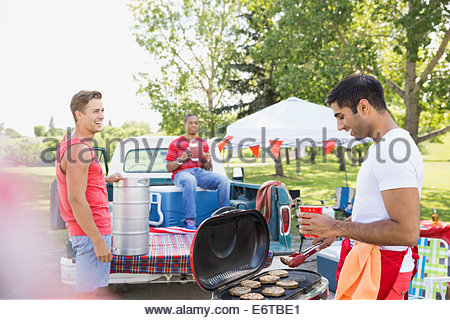 Men relaxing at tailgate barbecue in field - Stock Photo