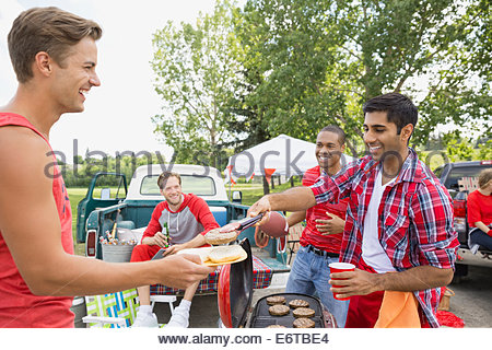 Men eating at tailgate barbecue in field - Stock Photo