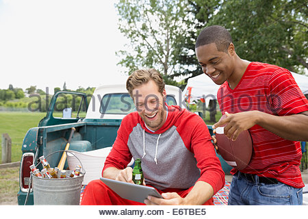 Men using digital tablet at tailgate barbecue - Stock Photo