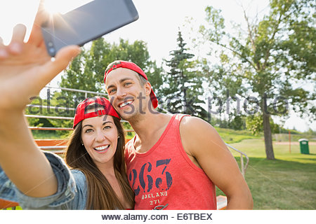 Couple taking cell phone pictures together in field - Stock Photo
