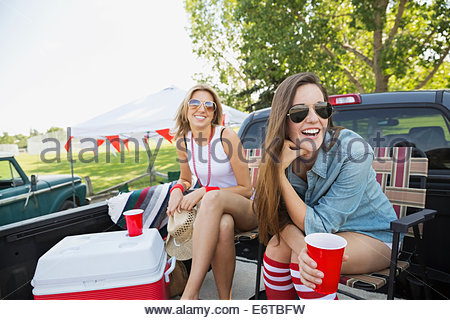 Women relaxing at tailgate barbecue in field - Stock Photo