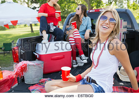 Woman relaxing at tailgate barbecue in field - Stock Photo