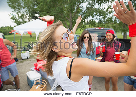 Woman dancing at tailgate barbecue in field - Stock Photo
