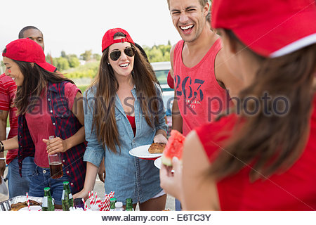 Friends relaxing at tailgate barbecue in field - Stock Photo