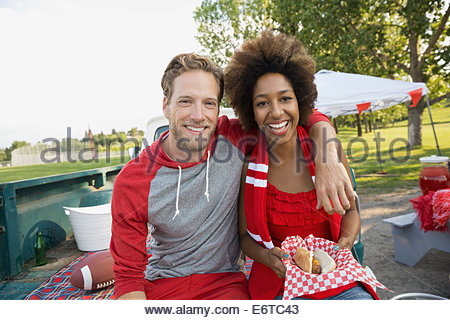 Couple smiling at tailgate barbecue in field - Stock Photo