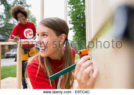 Volunteer measuring construction frame with tape measure - Stock Photo