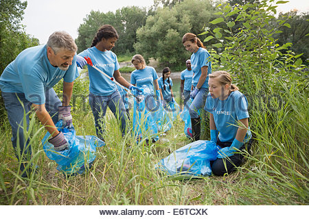 Volunteers picking up garbage in field - Stock Photo