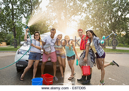 Portrait of friends washing car - Stock Photo