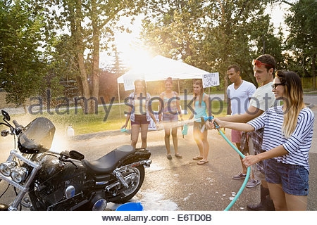 Friends washing motorcycle at charity car wash - Stock Photo