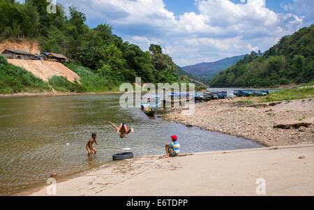 Riverboats and children along the Nam Ou river, at the village of Muang Ngoi Neua (also called Ban Ngoi Kao) in - Stock Photo