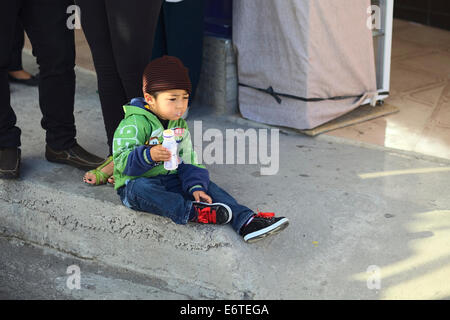 Unidentified young boy sitting on the sidewalk drinking yoghurt out of a plastic bottle in Catamayo, Ecuador - Stock Photo