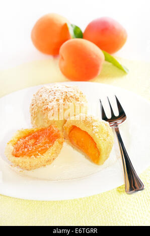 Dumplings with apricots on white plate - Stock Photo