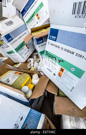 A pile of empty pesticide boxes containers and cans piled up in the corner of a farmer's barn. - Stock Photo