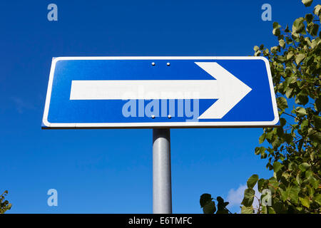 traffic sign arrow pointing right against blue sky - Stock Photo