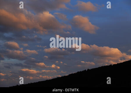 A photograph of some storm clouds being lit up from the side in orange by the setting sun. The photograph was taken - Stock Photo