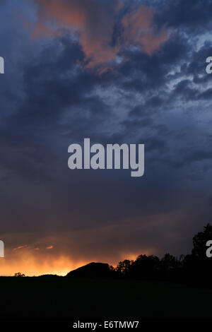 A photograph of some storm clouds being lit up from below in orange by the setting sun, creating a fiery effect. - Stock Photo