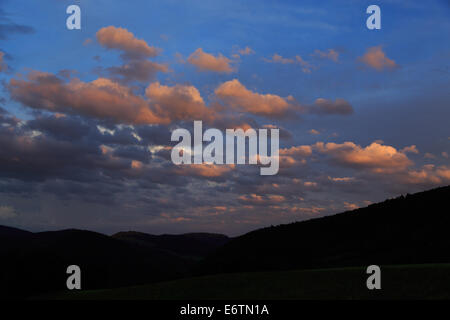 A photograph of some storm clouds being lit up from the side in orange by the setting sun. It was taken at sunset - Stock Photo