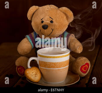 Sweet Teddy bear with cup of coffee, hot chocolate or tea and cookie in heart shape on brown wooden background. - Stock Photo