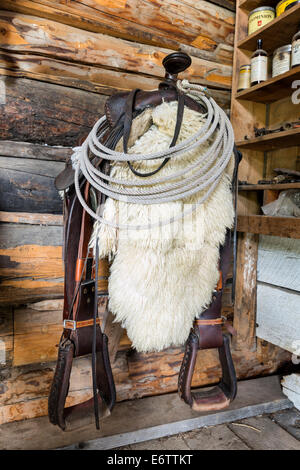 Saddle hanging in a horse barn, Bar U Ranch National Historic Site, Alberta, Canada - Stock Photo