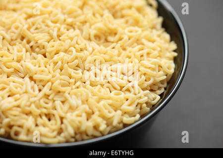 Raw alphabet soup pasta in a black bowl on black background. Close-up. - Stock Photo